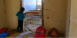 A Syrian child looks into a school classroom damaged during a reported air strike on March 7, 2017, in the opposition-held town of Utaya, near the city of Damascus.