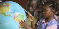 Children looking at a globe of the world in a classroom at school. Education in Guinea is free and designed to be compulsory for children aged between seven and 13. Credit: Giacomo Pirozzi/Panos.