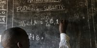 A teacher writes maths formulas on a blackboard at a school. Image Credit_Philippe-Lissac_Godong_Panos-Pictures