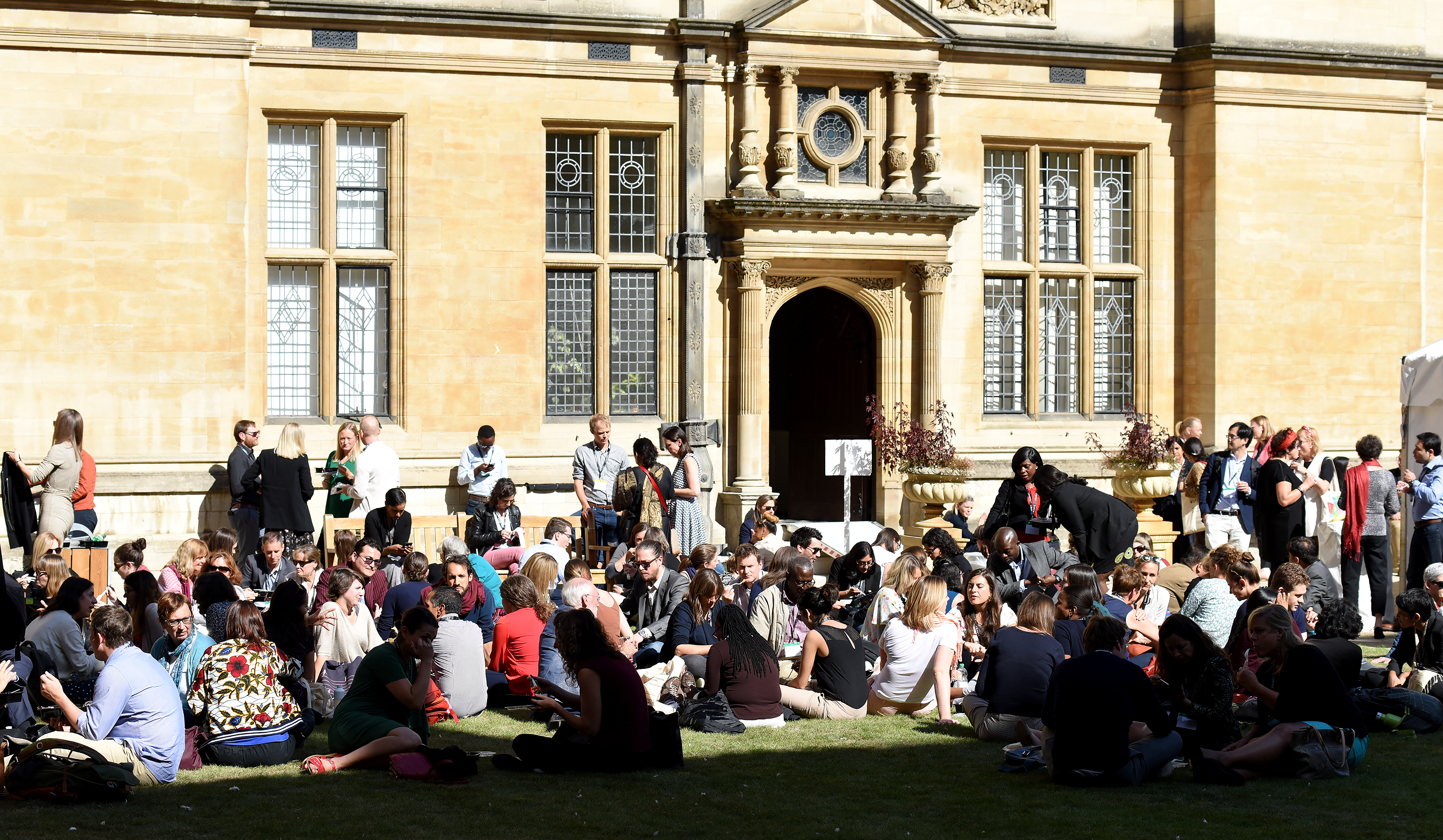 Conference delegates sitting on grass at lunchtime in the sunshine of the quod at Examination Schools