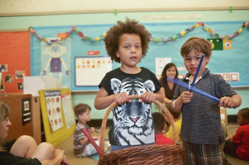 Boy with a basket in a primary school classroom, another boy has blue sticks