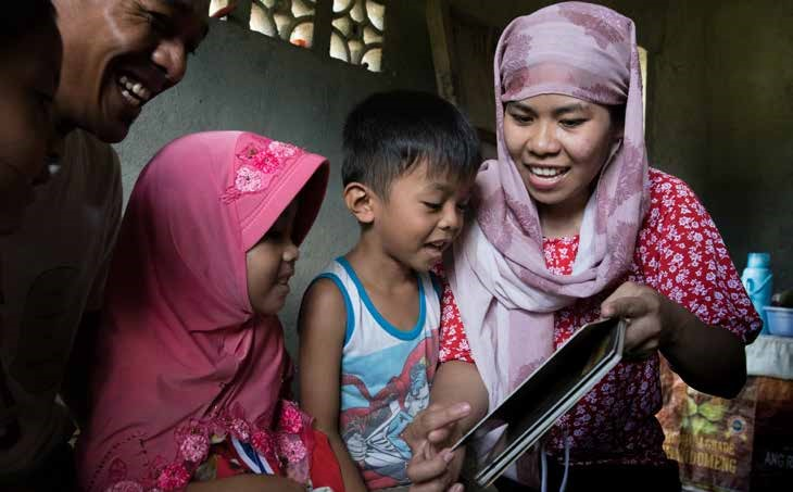 pre primary girl and her family read together at home, in Mindanao, Philippines