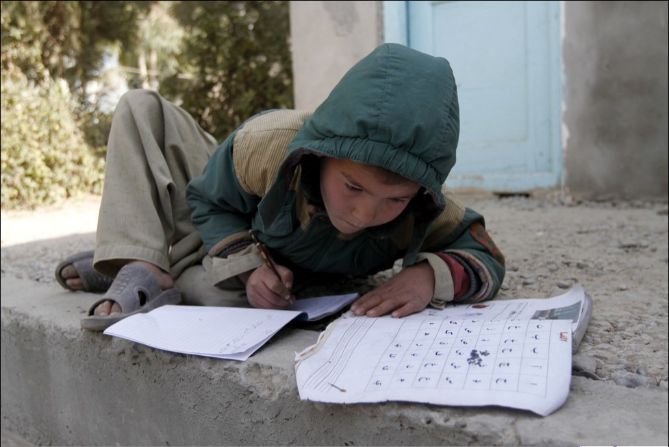 Boy in a coat with hood up working outside on school work