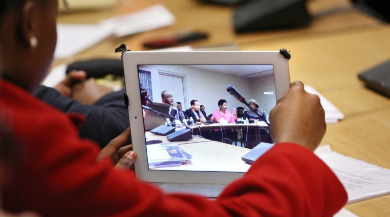 person watching a meeting via a tablet
