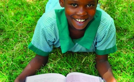 School girl in green uniform lying on her front on grass reading a book