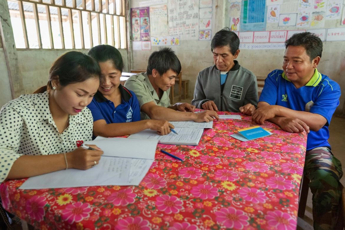 Teachers, the school principal and the village chief meet to discuss school finances and priorities. They are sitting around a table with a brightly coloured flowery cloth