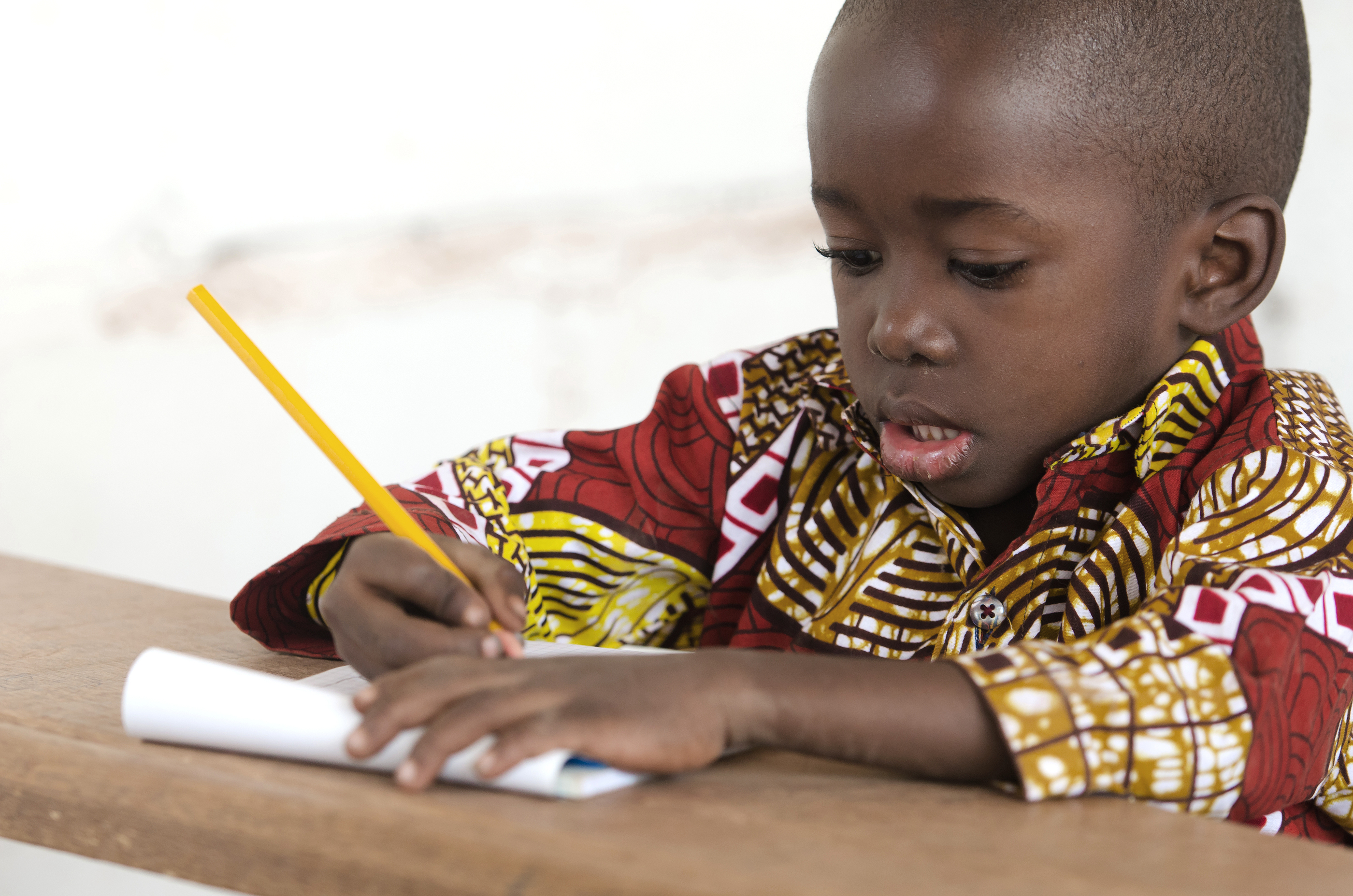 Primary age african boy writing with a yellow pencil
