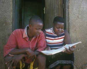Teenage girl and boy in Uganda, looking at text book