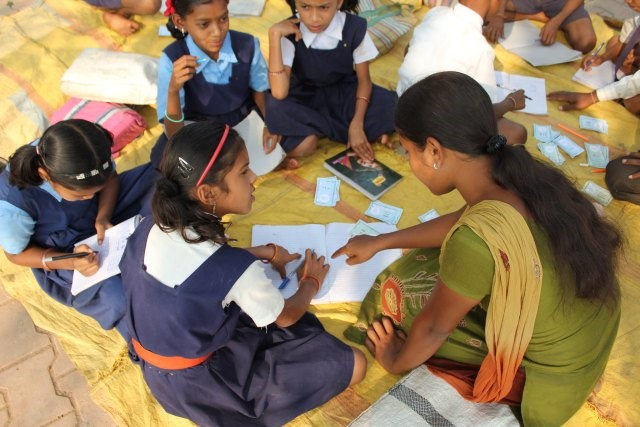 A group of Indian School children working on a yellow floor covering