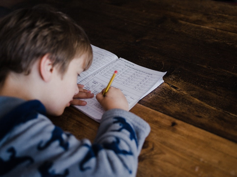 Child sitting at desk working on a workbook with a pencil