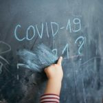 Child's hand on chalkboard on which is written COVID-19