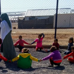 Adult and children playing in a refugee camp