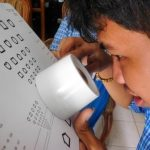 Cambodian child with magnifier taking a low vision assessment