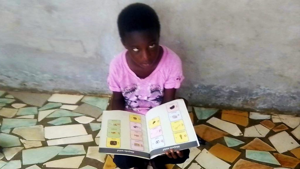 Blind girl in Senegal with books