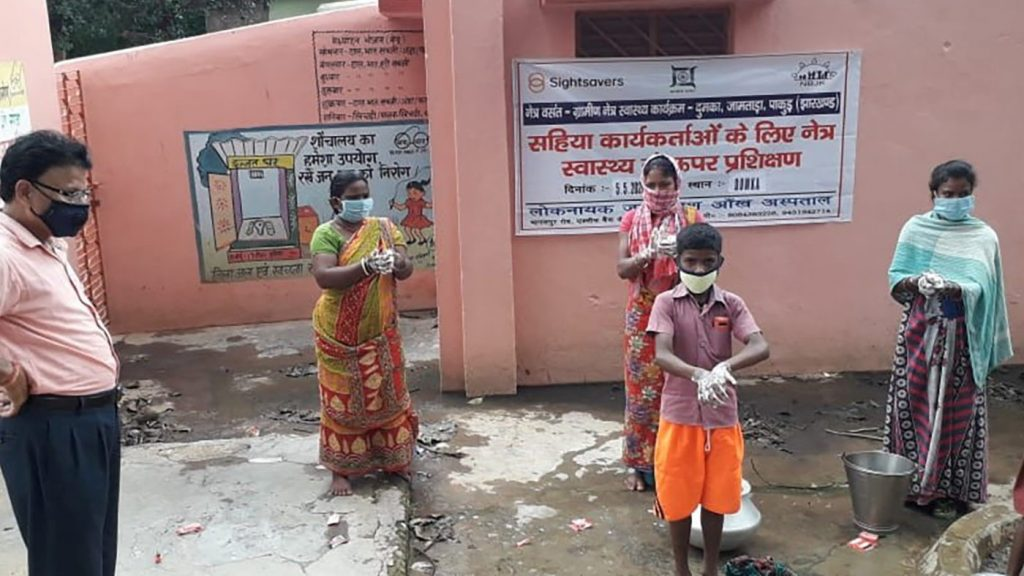 Indian community group of adults and children demonstrating PPE - gloves and masks and handwashing