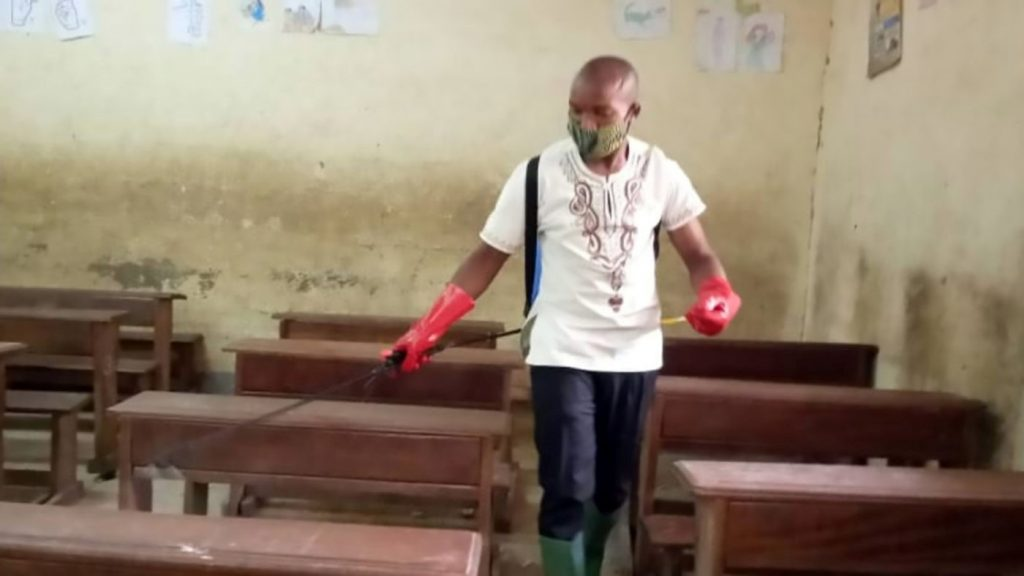 man disinfecting a classroom in Cameroon