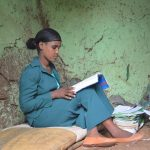 An Ethiopian grade 9 female student reading with a pile of books