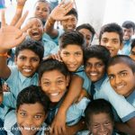A group of Indian school boys smiling and waving