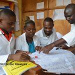 Rwandan mentor and teachers looking at learning materials