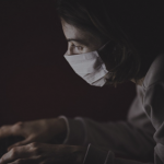 Dark image of person wearing a mask, looking at laptop