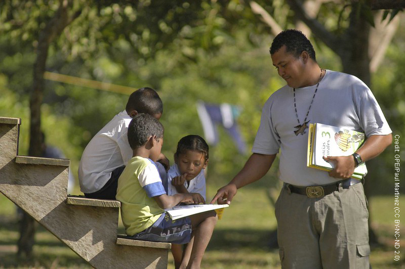 Teacher and student with book under a tree