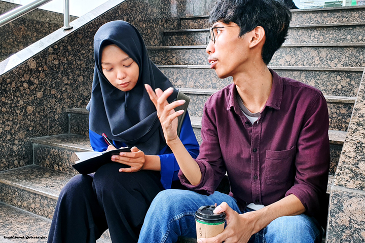 Two adult students in discussionm sitting on steps