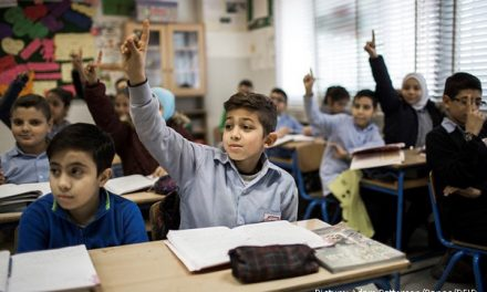 Children with their hands up in class in middle east school