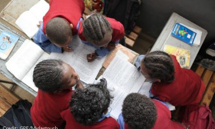 View from above of five children working on sheets and with textbooks in a classroom.