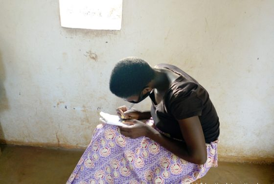 girl sitting writing, she is wearing a facemask