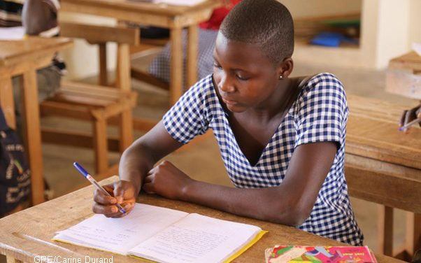 A girl working at a desk in Cote d'Ivoire, she is wearing a checked dress
