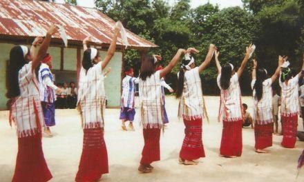 Women dancing in a village location wearing traditional dress