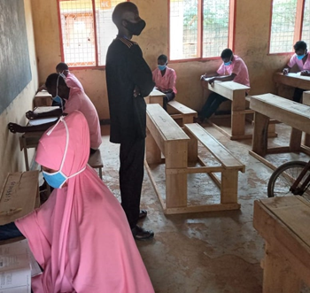 Children in pink uniforms and masks in an accelerated learning classroom in Kenya
