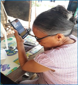 Woman sitting at a table with a mobile phone in  her hand