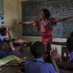 female teacher laughing with children in the classroom, Sierra Leone
