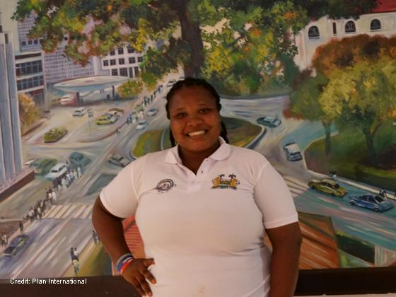 female teacher Famata in front of a mural of a street scene