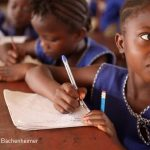Girl writing in her notebook in class, Sierra Leone