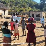 Teaching volunteer holds an informal community learning circle class outside in a rural village with social distancing and masks, Zimbabwe.