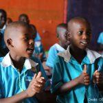 Children singing in the classroom of a primary school, Uganda