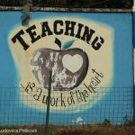 Sign reading 'Teaching is a work of the heart' on the wall of Freetown Teacher's College, Sierra Leone.